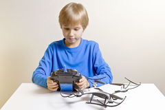 Little kid is going to play with the quadcopter drone at home. Boy holding a radio remote control. Technology, education, leisure, toys concept Royalty Free Stock Photography