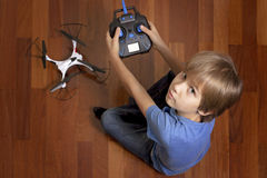 Little kid is going to play with the quadcopter drone at home. Boy sitting on the floor and holding a radio remote. Schoolboy is going to play with the Stock Photos