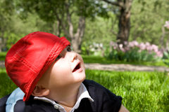 Little kid in grass. Surprised with something Stock Photo