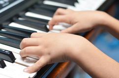 Little kid hand playing keyboard Stock Photo