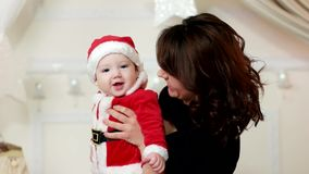 Little kid on the hands of the mother, the child dressed in a carnival costume of Santa Claus, a cute boy smiling mother stock footage