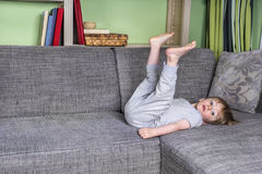 Little kid hanging around on the couch. Little bored boy laying on the couch Stock Image
