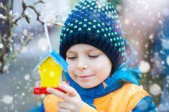 Little kid hanging bird house on tree for feeding in winter. Little kid boy feeding birds in winter. Child hanging colorful selfmade bird house on tree on frosty stock image