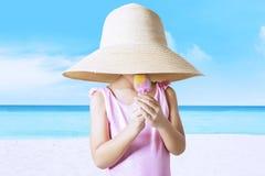 Little kid with hat licks ice cream at coast Stock Photo