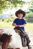 Little kid in hat on pony Stock Image