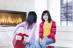 Little kid hides a gift for her mother Stock Photos