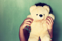 Little kid hiding behind teddy bear. selective focus. Stock Photos