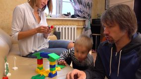 Little kid and his mom and dad playing with construction set at home together. 4K shot stock footage