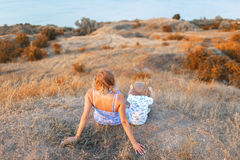 A little kid and his mother on a field background. A handsome family together enjoying a beautiful nature. Copy space. A photo of a lovely female and her Royalty Free Stock Images