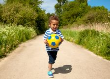 Little Kid Holding a Ball Stock Photography
