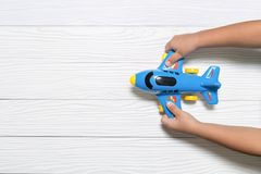 Little kid holding blue airplane toy. imagination concept.  stock photo