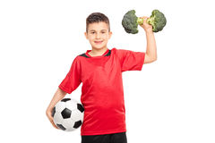 Little kid holding a football and broccoli dumbbell Stock Photography