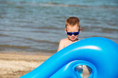Little kid holding an inflatable mattress on the beach on hot su Stock Photography