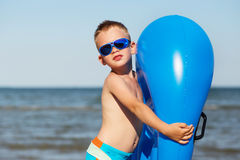 Little kid holding an inflatable mattress on the beach on hot su Royalty Free Stock Photos