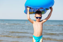 Little kid holding an inflatable mattress on the beach on hot su Stock Images