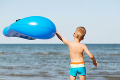Little kid holding an inflatable mattress on the beach on hot su Stock Photos