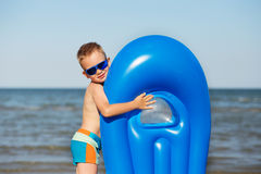 Little kid holding an inflatable mattress on the beach on hot su Stock Photo