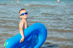 Little kid holding an inflatable mattress on the beach on hot su Royalty Free Stock Images