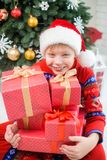 Little kid holding many red presents decorated with golden ribbo Stock Photography