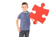 Little kid holding a piece of a puzzle. Isolated on white background stock images