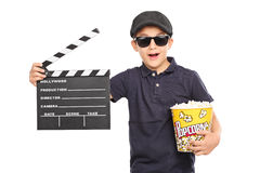 Little kid holding popcorn and a clapperboard. Little kid with a beret and sunglasses holding a box of popcorn and a movie clapperboard isolated on white royalty free stock image