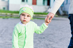 Little kid holds mom's hand. Stock Photo