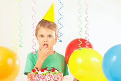 Little kid in holiday hat with birthday cake and balloons Royalty Free Stock Image