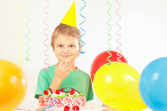 Little kid in holiday hat with festive cake and balloons Royalty Free Stock Photography