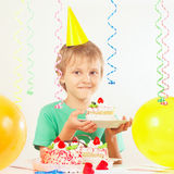 Little kid in holiday hat with piece of birthday cake and balloons Stock Photography