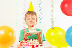 Little kid in holiday hat with piece of festive cake and balloons Stock Photo