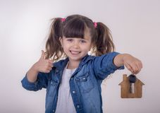 Little kid with house keys representing house purchase. A happy girl go to move to a new house and holds the keys to a new apartment royalty free stock photo