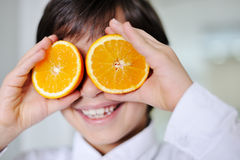 Little kid  hplaying with fresh orange Royalty Free Stock Image