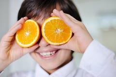 Little kid  hplaying with fresh orange Royalty Free Stock Image