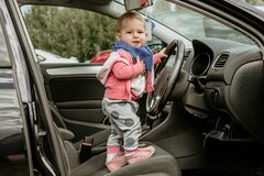 Free Little Kid In A Car. Stands In The Driver`s Seat And Holds The Wheel. The Car Door Is Open. Infant Driving. The Kid Looks Royalty Free Stock Photo - 180704375