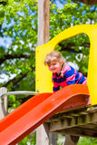Little Kid on a jungle gym slide Royalty Free Stock Photo