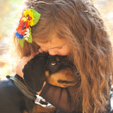 Little kid kissing and hugging puppy. Little kid kissing and hugging dachshund puppy. Love to animals concept stock photos