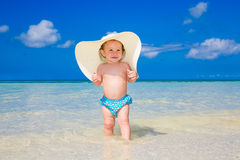 A little kid in a large white straw hat having fun on a tropical Royalty Free Stock Photo