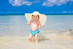 A little kid in a large white straw hat having fun on a tropical Stock Photos
