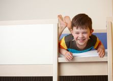 Little kid laughing on top of bunk bed Stock Images