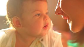 Little kid lies on the bed in the sun. Mom kisses her newborn baby. Kind bright frame. A cute little baby is looking into the camera and is happy on a white bed stock footage
