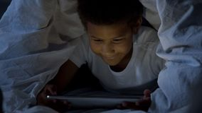 Little kid looking at tablet secretly at night, covered with head in blanket stock photo