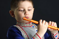 Little kid looking at wooden flute Stock Photos