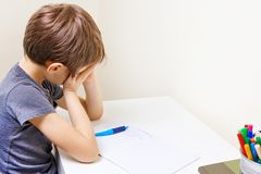 Little kid made his homework at home. The boy is tired and covers his face with hands. Tired child doing school homework at home royalty free stock photography