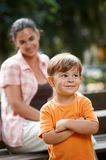 Little kid with mom standing arms crossed. Little happy casual caucasian kid with mom standing arms crossed. Parent in background, smiling. Looking up Royalty Free Stock Images