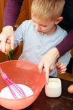 Little kid and mother cooking, making cake in bowl Stock Images