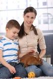 Little kid with mum caressing rabbit pet. Portrait of happy little kid with mum caressing cute rabbit pet, smiling Stock Image