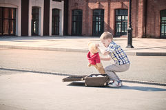 Little kid is opening the suitcase on the sunny street Stock Photo