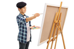 Little kid painting on a canvas. With a paintbrush isolated on white background stock photo