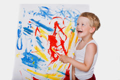 Little kid painting with paintbrush picture on easel. Education. Creativity Stock Images