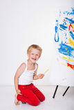 Little kid painting paints picture on easel. Education. Creativity Stock Photography